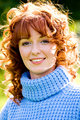 Bright portrait of red-haired young woman outdoors