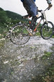 Mountain biker jumping over stream