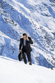 Businessman outdoors on snowy mountain using cellular phone