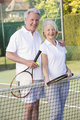 Couple playing tennis and smiling
