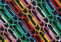Diagonal rows of colorful paper clips on black card.