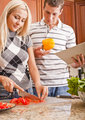Young Man Holding Book Next to Woman Cutting Tomato