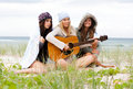 Young Women at the Beach With a Guitar