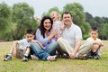 Portrait of happy family of five on the green land