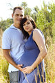 Man and pregnant wife in field