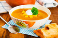 Pumpkin soup with cream in a bowl with painted flower and toast