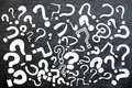 Various question marks on a blackboard