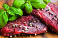 Beef steak on wooden board with basil