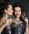 Christmas. Fashion women with wine glasses of champagne