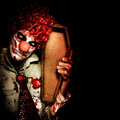Evil Horrible Clown Holding Coffin In Darkness