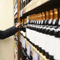 Man Choosing Wine Bottle From Shelves In Store
