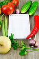 Notebook with vegetables and pepper