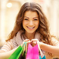 Young woman holding shopping bags at mall