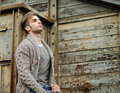 Attractive young man against rusty metal and wooden walls