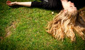 Young blonde woman lying on the grass.