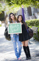 Mixed Race Female Students Holding Chalkboard With Back To Schoo
