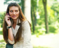 Young pretty woman on cellular phone, relaxing in the park