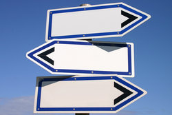 blank three way direction signpost with a blue sky background