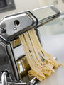 Fresh Egg Tagliatelle Being rolled in a Pasta Machine