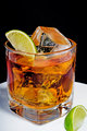Whiskey in a glass with ice cubes and slices of lime