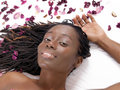 Young black woman reclining on sheet with flower petals