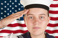 Young sailor saluting in front of US flag