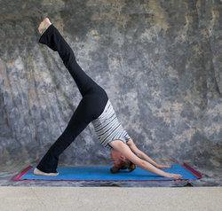 woman doing yoga posture eka pada adho mukha svanasana or