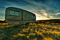 Camper trailer backlit by the sun during a beautiful sunset