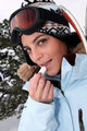 Skier applying lip balm