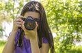 Young girl taking photos at summer green park