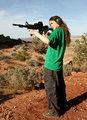 Teenage girl target shooting with rifle.