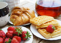 Tasty breakfast - tea, croissants, wafers with cream