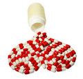 red and white capsules in the form heart, spilting from bottle.