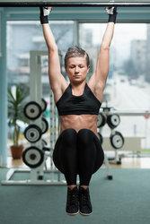 fitness woman performing hanging leg raises exercise stock